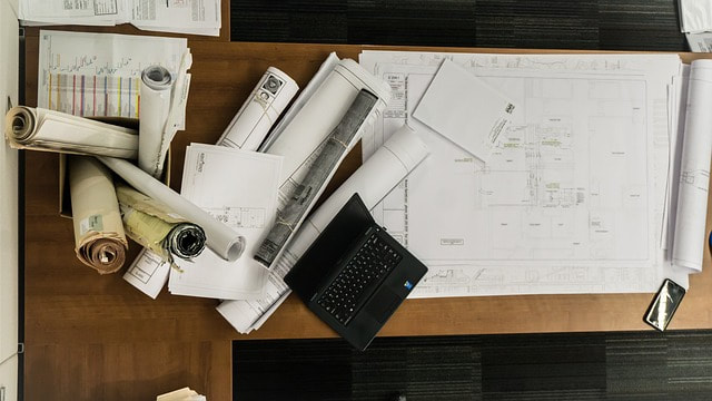 rolled up architectural drawings and computer sitting on office desk
